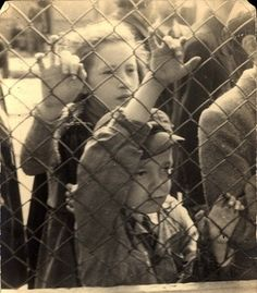Lodz, Poland, A boy and girl looking through the fence before their deportation.