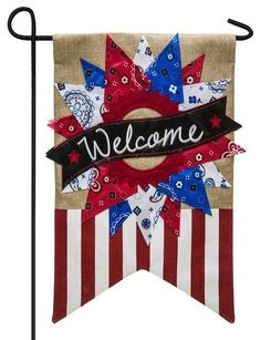This beautifully and brightly detailed, patriotic themed, burlap garden flag is enhanced with an abundance of embroidered and appliqued details. The wreath consists of triangular pieces of red, white