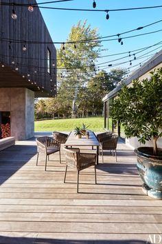 The deck features a table and armchairs by Kettal. String lights by Bulbrite   archdigest.com