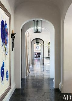 A large artwork by Sam Francis hangs in the hallway of Gisele Bündchen and Tom Brady's Los Angeles home, which is paved in antique Belgian bluestone; the Joan Behnke–designed lanterns and the sconce are by Paul Ferrante.