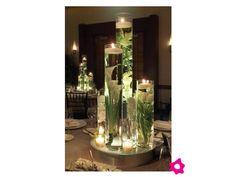 Cristalería cilíndrica con flores acompañada de pequeñas velas para el centro de mesa de tu boda.