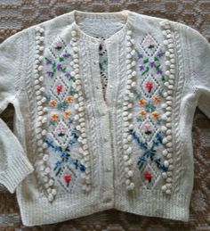 Tyrolean Sweater. There are a few precious sweaters that were knitted by my husband's mother and one of his two delightful and eccentric great aunts. One of her sweaters is a cream wool Tyrolean-style cardigan with vertical columns of beautifully embroidered flowers between the columns of cables, bobbins, and eyelets. You probably know the style. No one does this much anymore because of the labor involved. It is a gem.