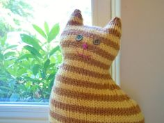 This is the first in my series of house cats!The Window Cat is a simple pattern knit in the round from the bottom up. Tail and paws are knit separately, also in the round, and seamed to the body. Finishing touches (eyes, nose and whiskers) can be embroidered on or embellished with buttons, fabric, etc. There is no end to the ways that this cat can be personalized!~Dimensions of finished cat are about 12 inches by 7 inches.