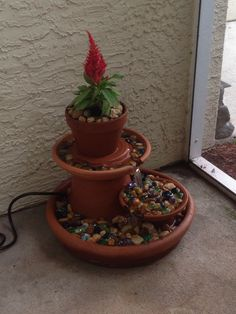 DIY clay pot fountain. Fountain pump - $10 from Lowe's. Assorted clay pots from Walmart. Clay base from Home Depot- deeper the better! River rock from Lowe's. All together around $35.
