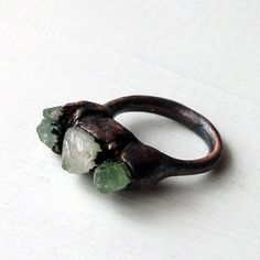 Copper ring features three shards of rough tourmaline from Brazil - in various shades of green. All three are uniquely set and encompassed by a very sculptural, electroformed copper band that follows the contour of the stones. All of my works are unique one off pieces and completely handmade in my studio. Ring Size: US 7 Stone setting approx. size 3/4 x 1/2 (WxH) **Each piece has been electroformed in copper and then blackened with LOS. For complete information regarding the pro...