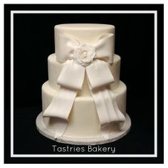 White Wedding Cake with a Large White Bow and Fondant Rose from Tastries Bakery, Bakersfield Bakery.