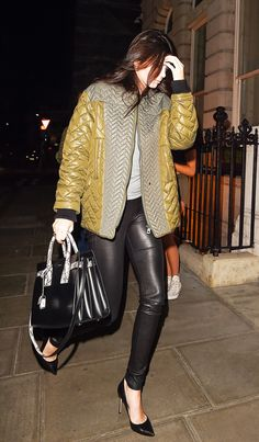 Kendall Jenner wears an oversized mustard yellow puffer jacket, grey shirt, leather pants, black pointed toe heels and a black structured bag.