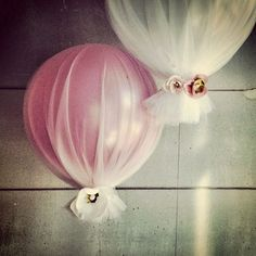 Balloons covered in tulle and decorated with tiny synthetic flowers.