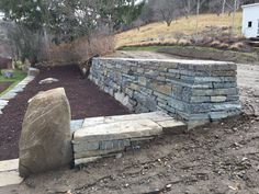 This stone wall was built with an excavator following the practices used by the D.S.W.A. Dry Stone Walling Association. Built by Hector Santos