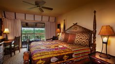 A wooden-framed king bed across from a desk with chair Jambo House Villa Disney World Resorts, Walt Disney World, Disney Planning, King Beds, Animal Kingdom, Vacations, Villa, Desk, Chair