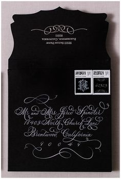Silk invitations made of silver dupioni with a black embroidered monogram. These luxurious wedding invitations were engraved with a beveled and hand painted edge.   Our lace custom invitations come with lace bands to hold in the inserts. The invitations were mailed in unique envelopes with white calligraphy. Please to click on the photo to see all of the details or pin to save for later!