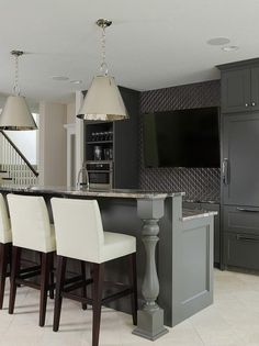 Sleek basement bar features black cabinets paired with gray granite ocuntertops and a gray geometric tile backsplash.