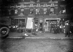 NYC CRIME SCENE: Sometime between 1916 and 1920. A male victim is on the sidewalk as tenement dwellers look on from their windows. First floor shops include a pasta maker, olive and wine importer and laundry.
