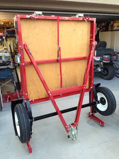 Folding trailer in folded position, ready for storage. Unfold it and hook it up when you need a trailer to haul stuff. Holds up to 1,175 pounds. From Harbor Freight. Assembly required.