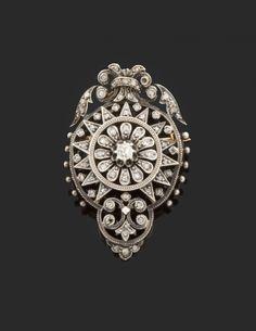 Broche pendentif rosace à volutes et feuillages sertie de diamants taille rose. Monture en or jaune et argent. Vers 1880.