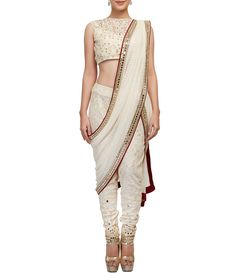 This  off-white sleeveless blouse embellished blouse with mirror and pearl embroidery, matching thick lace fitted pants with mirror and sequin embellishment and self stripe saree drape with mirror border.