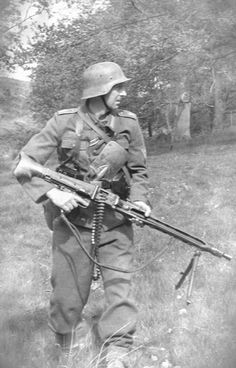 MG-42 in action with 50-round belt loaded. A common practice when moving with the LMG. Note the trench shovel inside the belt. The short handled shovel was much more commonly used than knives for hand to hand combat in WWII, mostly on the Russian front.