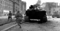 Soldiers of 2nd Regiment (HQ Group) First Special Service Force run past a burning Tiger tank. Taken near outskirts of Rome, June 4, 1944