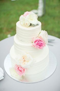A simple, but elegant 3-tiered white wedding cake decorated with pink and white roses. Wedding coordinated by Moana Events. #weddingcake #hawaiiweddings #destinationweddings