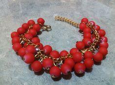 Pulsera de cadena color oro, y perlas rojas.