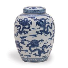 This porcelain jar is adorned with a classic Asian pattern of hand painted dragons. The timeless piece measures 14