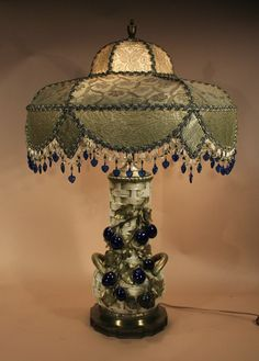 """Antique Lamp. Pancake diamond shape shade is cream and olive toned, covered with metallic shot lace and then hung with looped beaded fringe around the bottom edge. The beads reflect the rich cobalt blue tones of the highly dimensional plums """"growing"""" off and around the large, basket-weave, Amphora table lamp."""