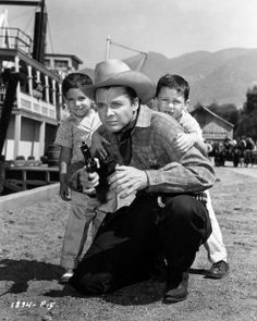 Terry and Skipper seek protection behind dad Audie Murphy as they strike a pose familiar to Western fans on the set of Ride a Crooked Trail