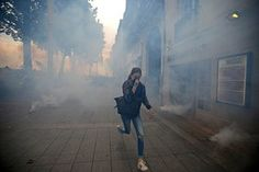 Nantes, France: A woman runs from teargas after clashes with riot police during…