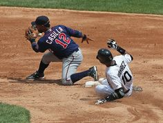 Alexei Ramirez #10 of the Chicago White Sox slides into second base beating the throw to Alexi Casilla #12 of the Minnesota Twins at U.S. Cellular Field on July 25, 2012 in Chicago, Illinois.