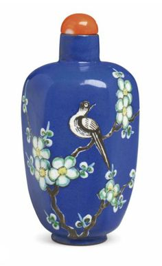 A RARE ENAMELED BLUE-GROUND SNUFF BOTTLE   Yixing, 1800-1870   The hexagonal bottle is enameled with a magpie resting in the branches of a prunus tree with its head turned to gaze at its partner in flight, all reserved on a deep blue ground.  2¾ in. (7 cm.) high, coral stopper