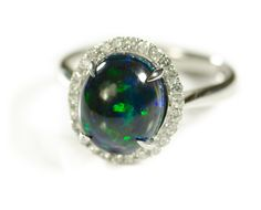BLACK OPAL, DIAMOND AND WHITE GOLD RING. The 14k white gold ring set with round-cut diamonds forming a frame around an oval black opal cabochon weighing approximately 2.55 cts. Total estimated weight for all diamonds: 0.31 cttw. Ring size: 7.Estimated to sell between $800-1200. To be sold as lot 0514-0103.