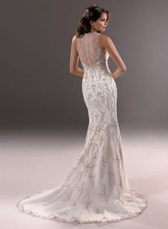 Blakely - by Maggie Sottero The lavish embroidery and sparkling beads of this fit and flare gown capture the dramatic flair of a bygone era. Finished with scalloped illusion neckline, and button over zipper back closure. Colors Available Ivory/Silver accent, Ivory/Gold accent (shown), Gold
