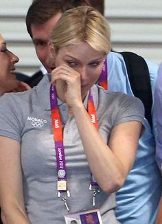 The South African wipes away tears of pride as her country's National Anthem is played.