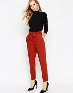 ASOS women's business casual pants in red with tie around waist. Black high neck sweater.
