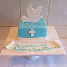 A simple and elegant christening cake for a little boy, complemented with a hand cut fondant dove and crucifix