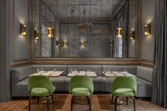 The brass lights, grey walls and booth and apple green chairs a beauty of a combo!