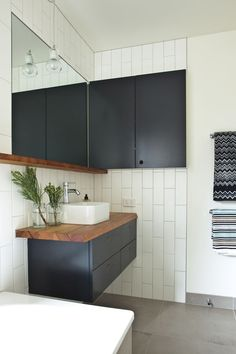 Black and white bathroom with spruce branches by sink // subway tile on walls