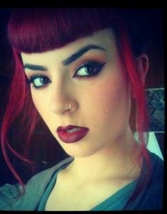 Red hair with short bangs and ombre lips.