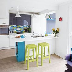 Small kitchen with blue and green splashback tiles, white cabinetry, white island unit, blue shelving and lime bar stools