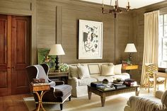 The study's lime-washed paneling, made of oak reclaimed from the property, is complemented by a gilt-wood chandelier by Vaughan; a Suzanne Kasler for Hickory Chair sofa is joined by a Scalamandré wing chair upholstered in a Rogers & Goffigon velvet, and the antique armchair is clad in an Old World Weavers tiger stripe.