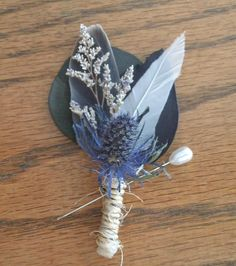 This boutonniere was inspired by the fog covered river. Shades of grey, blue, charcoal, and white combine to create a serene, unique boutonniere. Best of all, every element of this item is natural- dried eucalyptus leaves, feathers, and dried flowers. The stem is bound with a natural sisal cord that has a wonderful rustic look. $12 on Etsy