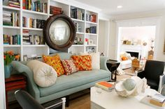 love the blue & orange together. Love the oversized neckroll on the sofa. and the mirror on the bookshelves is great.