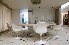 The dining room of Eero Saarinen's Miller House in Columbus, Indiana is naturally furnished with his tulip chairs.  Great floor pattern and table top decorations designed by Alexander Girard.   What type marble is used on the back wall?