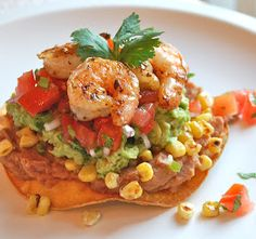 Shrimp & Avocado Tostada- Baked tortilla, refried beans, corn, spiced shrimp, avocado,& Pico de gallo