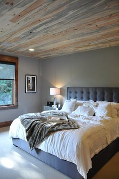 Like the wood planks on the ceiling. Gray walls, gray padded headboard + fresh white bedding.