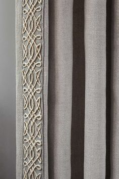 Neutral linen curtain with a braid trim on the leading edge. Samuel and Sons Passementerie