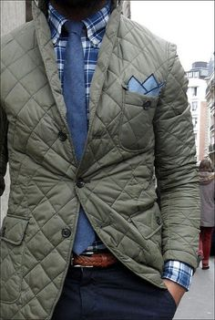 Team an olive quilted jacket with navy chinos for a trendy and easy going look. Shop this look for $145: http://lookastic.com/men/looks/chinos-and-belt-and-jacket-and-pocket-square-and-tie-and-longsleeve-shirt/4144 — Navy Chinos — Brown Leather Belt — Olive Quilted Jacket — Light Blue Pocket Square — Navy Tie — Navy and White Plaid Longsleeve Shirt