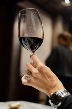 Woman's hand holding a glass of red wine.