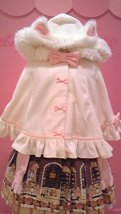 Cute, sweet lolita: Light pink poncho with fuzzy details, frills and ears. Pink bow. Brown skirt with pattern.