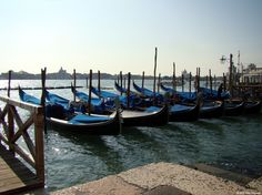 An early-morning shot of a small fleet of gondolas, about to be available for business. Scene on the Grand Canal, San Marco.
